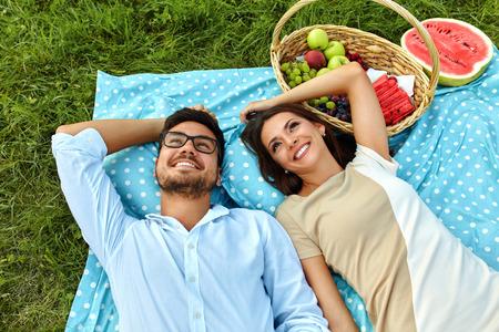 femme romantique: Couple Happy In Love On pique-nique romantique dans le parc. Belle jeune femme et souriant Homme Beau Allongé sur Blanket, détente, profiter de la nature et passer du temps ensemble à l'extérieur. Relations Concept
