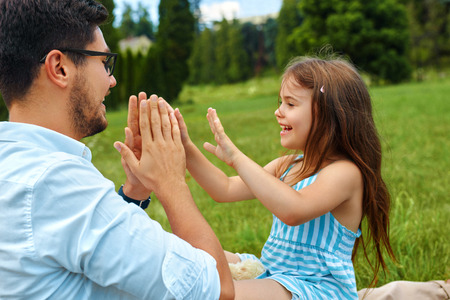 family relationships: Father And Daughter Having Fun. Happy Smiling Young Dad Playing Hand Clapping Game With His Kid. Parent And His Child Laughing And Relaxing Outdoors In Nature. Family Relationships Concept