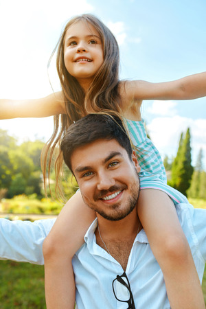 Happy Father And Child Having Fun Playing Outdoors. Smiling Young Dad And Daughter Spending Time Together In Nature. Parent And His Kid Relaxing In Park. Family Time, Relationships Concept