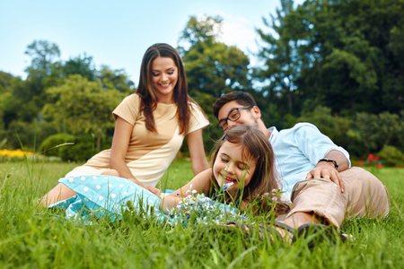 family relationships: Happy Young Family On Picnic In Park. Smiling Parents And Children Having Fun, Playing, Spending Leisure Time Together In Nature. Kids And Adults Relaxing Outdoors On Weekend. Relationships Concept
