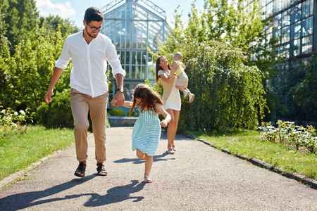 family playing: Family Having Fun Outdoors. Beautiful Happy Smiling Young People And Their Children Playing Together In Garden. Parents And Kids Spending Leisure Time Together Outside. Love And Relationships Concept Stock Photo