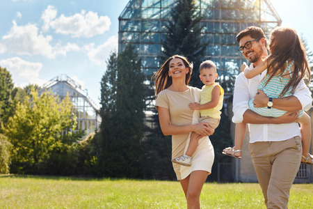 family relationships: Happy Family Portrait In Nature. Beautiful Smiling Young Parents And Children Spending Time Together In Park. Mother, Daughter, Father And Son  Having Fun Outdoors. Love And Relationships Concept. Stock Photo