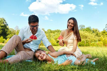 family time: Family In Park. Happy Beautiful Young Parents And Smiling Child Having Fun On Picnic In Park, Kid Eating Fruits. People Relaxing And Spending Time Together Outdoors, In Nature. Relationship Concept