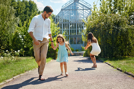 family relationships: Family Having Fun Outdoors. Beautiful Happy Smiling Young People And Their Children Playing Together In Garden. Parents And Kids Spending Leisure Time Together Outside. Love And Relationships Concept Stock Photo