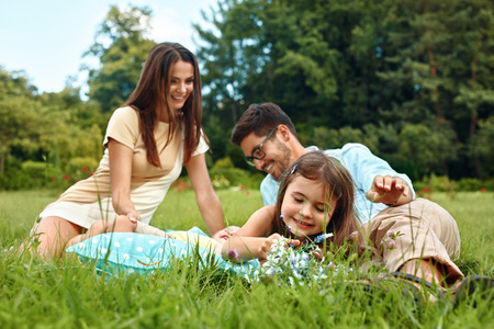 family happy: Happy Young Family On Picnic In Park. Smiling Parents And Children Having Fun, Playing, Spending Leisure Time Together In Nature. Kids And Adults Relaxing Outdoors On Weekend. Relationships Concept