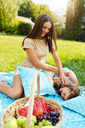 tickling: Mother And Daughter Having Fun In Park. Beautiful Happy Smiling Young Mom Tickles Child While Relaxing Together In Nature. Parent Tickling Kid While Playing Outdoors. Family Relationships Concept