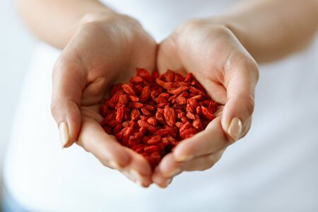 Organic Diet Food. Closeup Of Young Woman Hands With Natural Nails Holding Tasty Ripe Sweet Red Sun Dried Goji Berries, Natural Vitamin Snack. Healthy Nutrition, Raw Eating Concept. High Resolution