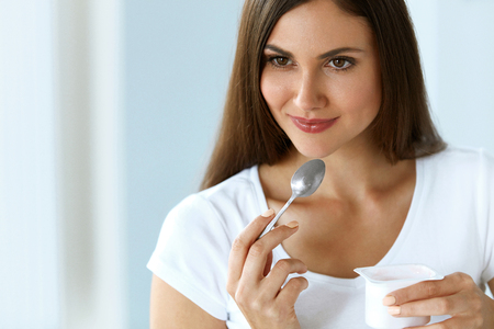 Healthy Diet And Nutrition. Close-up Beautiful Sexy Smiling Young Woman Eating Natural Yogurt. Portrait Of Happy Girl Tasting Organic Yoghurt, Dairy Product. Weight Loss Food Concept. High Resolution Stock Photo