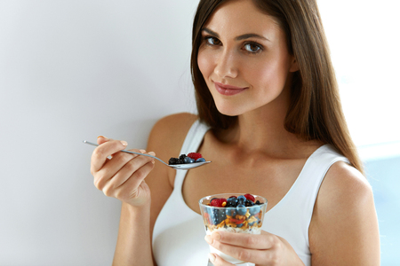Female On Healthy Diet. Close-up Of Smiling Young Woman With Glass Of Organic Yogurt, Fresh Berries And Raw Muesli. Beautiful Happy Girl Eating Diet Yoghurt Oats Dessert For Breakfast. High Resolution
