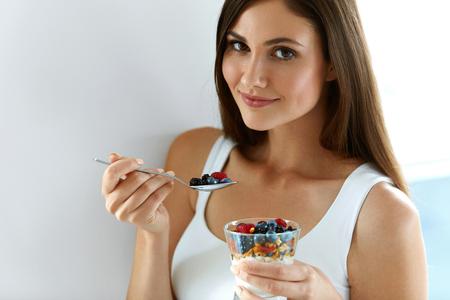 Kobieta na zdrowej diety. Close-up Uśmiechnięta Młoda Kobieta Z Szampana Organicznego Jogurt, świeże Jagody I Raw Muesli. Beautiful Girl Szczęśliwy Jedzenie Dieta Jogurt Oats Deser Na śniadanie. Wysoka rozdzielczość