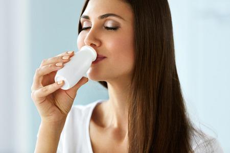 yogurt: Bebida saludable. Primer hermoso de la muchacha sonriente de yogurt orgánico potable. Retrato de mujer joven sostiene una botella de Natural yogur para beber, productos lácteos. Las bebidas de dieta Concepto. Alta resolución Foto de archivo