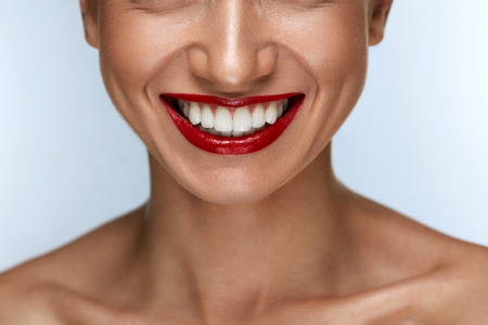 건강 한 흰색 치아와 빨간 입술 아름 다운 미소. 완벽 한 빨간 립스틱 메이크업을 가진 통 통 전체 입술에 웃는 여자 입의 근접 촬영. 치아 미백, 치과  스톡 콘텐츠