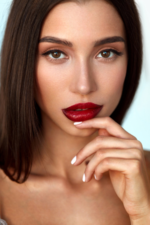 Beauty Face. Beautiful Young Woman With Red Lipstick On Full Sexy Lips And Perfect Smooth Soft Skin. Closeup Of Fashion Make-up Model Girl With Professional Makeup. Cosmetics Concept. High Resolution