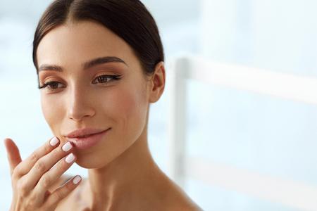 Lips Skin Care. Mooie Vrouw Met Gezicht van de Schoonheid toepassen van lippenbalsem, Lippenbalsem Op Volle Sexy Lips. Portret van glimlachende vrouwelijke model met zachte huid en natuurlijke make-up Naakt Touching Lips. Hoge resolutie Stockfoto