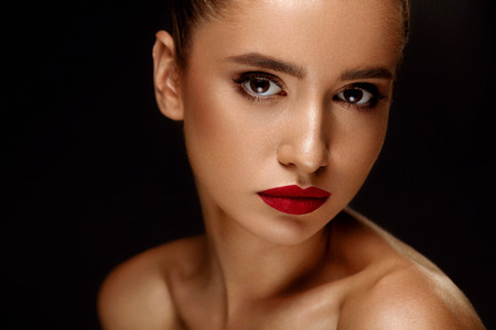 Fashion Beauty Woman Portrait. Beautiful Girl Face With Perfect Smooth Soft Skin And Professional Makeup. Closeup Of Fashionable Female Model With Red Lipstick On Lips And Smoky Eyes. High Resolution