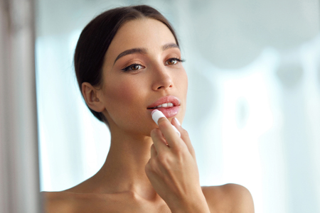 lip stick: Lips Protection. Beautiful Woman With Beauty Face, Sexy Full Lips Applying Lip Balm, Lipcare Stick On. Portrait Of Female Model With Natural Makeup. Lips Skin Care Cosmetics Concept. High Resolution
