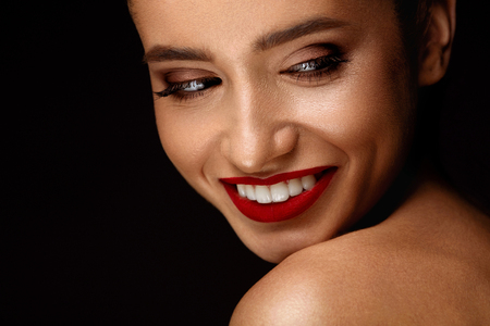 glamourous: Fashion Makeup Model. Portrait Of Beautiful Glamourous Young Woman With Perfect Makeup, Long Eyelashes, Red Lips And Smooth Skin. Sexy Girl With Beauty Face On Dark Background. Cosmetics Concept Stock Photo