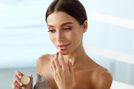 Lips Skin Care. Beautiful Woman With Beauty Face Applying Lip Balsam, Lipbalm On Full Sexy Lips. Portrait Of Smiling Female Model With Soft Skin And Natural Nude Makeup Touching Lips. High Resolution Stock Photo
