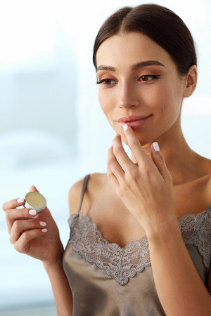balm: Lips Skin Care. Beautiful Woman With Beauty Face Applying Lip Balsam, Lipbalm On Full Sexy Lips. Portrait Of Smiling Female Model With Soft Skin And Natural Nude Makeup Touching Lips. High Resolution Stock Photo