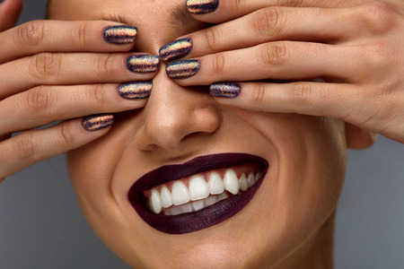Fashion Makeup. Closeup Of Beautiful Fashionable Woman Closing Eyes With Hands With Dark Glitter Nails. Sexy Smiling Girl With Dark Lipstick On Lips, White Teeth And Perfect Smile. High Resolution