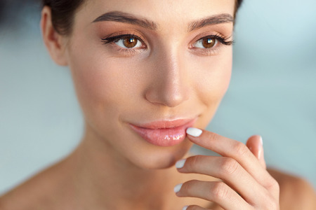 Beauty Face. Beautiful Woman With Natural Makeup And Sexy Full Lips Touching Her Mouth. Closeup Portrait Of Smiling Model Girl With Healthy Smooth Facial Skin Applying Lip Balm On Lip. High Resolution Stock Photo