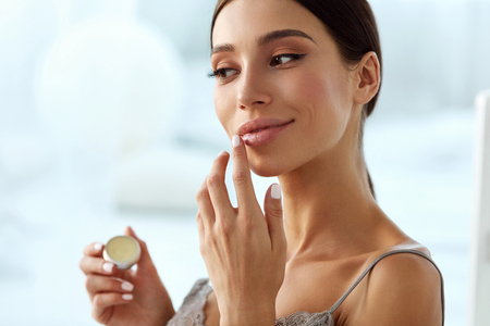 Lips Skin Care. Beautiful Woman With Beauty Face Applying Lip Balsam, Lipbalm On Full Sexy Lips. Portrait Of Smiling Female Model With Soft Skin And Natural Nude Makeup Touching Lips. High Resolution Standard-Bild