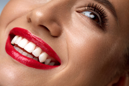 Beauty Fashion Woman Face With Perfect Smile. Closeup Of Beautiful Sexy Girl Face With Bright Makeup. Smiling Young Female Model With Smooth Skin, Long Eyelashes, Red Lips And Healthy White Teeth