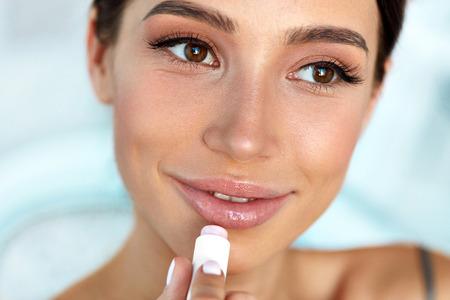 唇保護。美容顔、セクシーな唇に Lipcare スティックのリップ クリームを適用すると美しい女性。ナチュラルメイクの女性モデルのポートレート。唇 写真素材