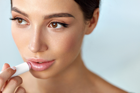 Lips Protection. Beautiful Woman With Beauty Face, Sexy Full Lips Applying Lip Balm, Lipcare Stick On. Portrait Of Female Model With Natural Makeup. Lips Skin Care Cosmetics Concept. High Resolution