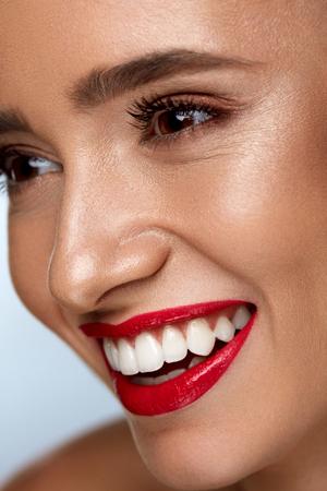 美容ファッション女性顔完璧な笑顔を持つ。明るい化粧とセクシーな美少女顔のクローズ アップ。滑らかな肌、長いまつげ、赤い唇、健康な白い歯