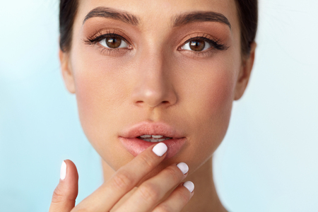 Lips Skin Care. Beautiful Woman With Beauty Face Applying Lip Balsam, Lipbalm On Full Sexy Lips. Portrait Of Female Model With Soft Skin And Natural Nude Makeup Touching Lips. High Resolution