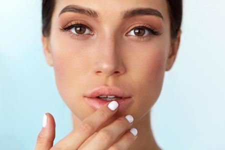 Lips Skin Care. Mooie Vrouw Met Gezicht van de Schoonheid toepassen van lippenbalsem, Lippenbalsem Op Volle Sexy Lips. Portret van vrouwelijk model met zachte huid en natuurlijke make-up Naakt Touching Lips. Hoge resolutie