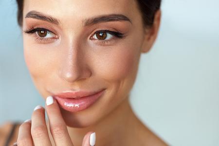 美容顔。自然なメイクと彼女の口に触れる唇セクシーな美しい女性。唇にリップ クリームを適用する健康的な滑らかな肌とモデルの女の子の笑顔の