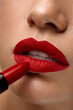 red lip: Red Lips. Closeup Of Woman Face With Bright Red Matte Lipstick On Full Lips. Beautiful Girl Applying Rouge Lipstick OnmSexy Soft Plump Lip. Beauty Cosmetics And Makeup Concept. High Resolution Image Stock Photo