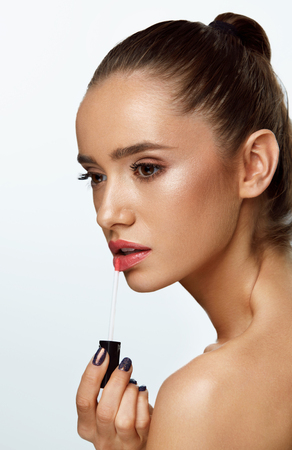 Woman Beauty Face With Makeup. Closeup Portrait Of Sexy Girl With Smooth Skin, Beautiful Facial Make-up Applying Lip Gloss On Lips. Fashion Female Model Putting Lipbalm On Lip. High Resolution Image Stock Photo