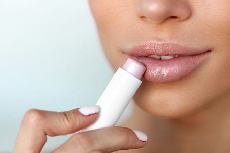 hygienic: Lips Skin Care. Beautiful Woman Face With Sexy Full Lips Applying Hygienic Lip Balm, Lipcare Stick. Closeup Of Female Face With Soft Skin Putting Lip Protector Lipstick On. Beauty Cosmetics Concept