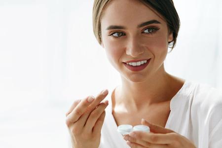 Augengesundheit. Portrait der jungen schönen Frau mit natürlichen Make-up und Kontakt Augen-Objektiv in der Hand. Nahaufnahme des weiblichen Model Holding White Gläserkasten. Augenpflege und gesunde Lebensweise. Hohe Auflösung Bild. Standard-Bild
