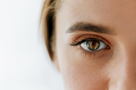 high view: Eye Health And Care. Closeup Of Beautiful Woman Big Brown Eye And Eyebrow. Girl Eye Smooth Healthy Skin And Perfect Natural Makeup On White Background. High Resolution Image