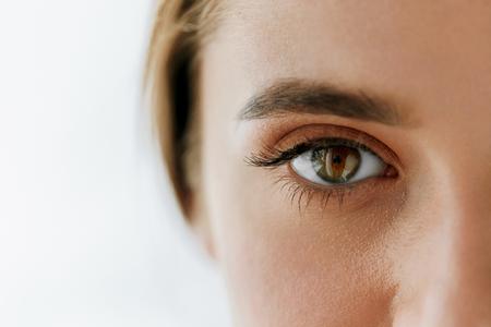 Salud de los ojos y la atención. Detalle de hermosa mujer de ojos grandes de Brown y la ceja. Chica de ojos liso de la piel sana y maquillaje natural perfecto en el fondo blanco. Imagen de alta resolución
