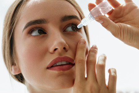 Vision And Ophthalmology Medicine. Closeup Of Beautiful Woman Applying Eyedrops In Her Eyes. Young Female Model With Natural Makeup Using A Bottle Of Eye Drops. Health Concept. High Resolution Stok Fotoğraf - 68983734