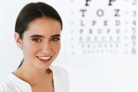 Optometry And Vision. Portrait Of Beautiful Smiling Girl Face At Opthalmologist Office. Closeup Of Happy Young Woman With Healthy Eyes And Visual Eye Test Chart On Background. High Resolution Image Stock Photo