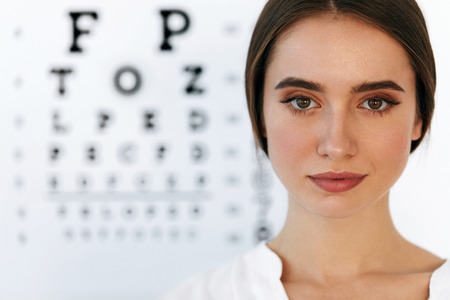 Visual Health. Healthy Smiling Female Doctor With Beautiful Face At Ophthalmologist Office. Portrait Of Young Woman In Front Of Visual Eye Test Chart. High Resolution Image.