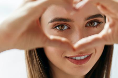 건강한 눈과 비전. 아름 다운 행복 한 여자 마음을 잡고의 초상화는 손 가까이에 눈 모양. 사랑의 기호를 표시하는 건강한 피부와 웃는 소녀의 근접 촬 스톡 콘텐츠
