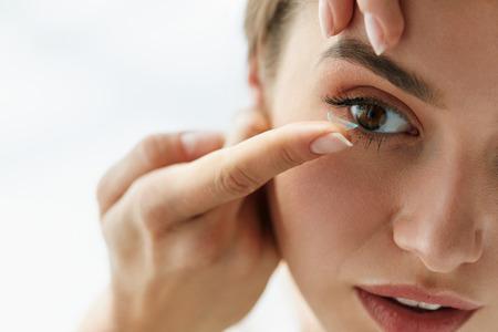 lentes de contacto: Póngase en contacto con la lente para la visión. Primer plano de la cara femenina con la solicitud Lente de contacto en sus ojos castaños. Hermosa mujer de colocarse los lentes del ojo con las manos. Medicina oftalmología y salud. Alta resolución Foto de archivo