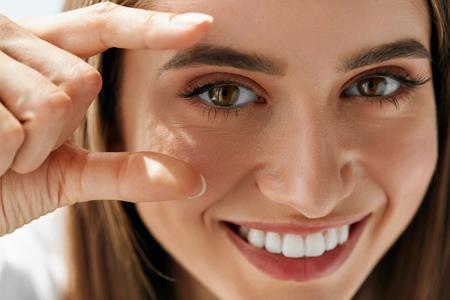 健康 Eyevision。彼女の目に焦点を当てると美しい幸せな女。陽気な外観、自然なメイクと滑らかな肌を持つ少女の笑みを浮かべてのクローズ アップ。