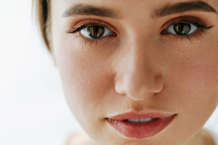 Eye Health And Care. Portrait Of Girl Face With Smooth Healthy Skin And Perfect Natural Makeup. Closeup Of Beautiful Woman With Big Brown Eyes And Eyebrows On White Background. High Resolution Image