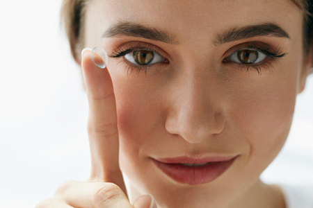 Eye Care And Contact Lenses For Eyes. Closeup Of Beautiful Woman Face With Smooth Skin And Perfect Makeup Applying Eyelens With Finger. Female Model Putting In Contact Eye Lens. Vision And Health Banque d'images