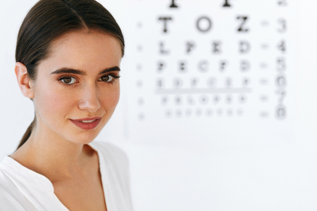 schöne augen: Optometry And Vision. Portrait Of Beautiful Smiling Girl Face At Opthalmologist Office. Closeup Of Happy Young Woman With Healthy Eyes And Visual Eye Test Chart On Background. High Resolution Image Lizenzfreie Bilder