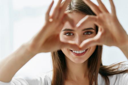 Gesunde Augen und Vision. Portrait der schönen Frau glücklich Halten Herz-geformte Hände in der Nähe Augen. Nahaufnahme des lächelnden Mädchen mit gesunder Haut Zeigen von Liebe Zeichen. Augenpflege. Hohe Auflösung Bild