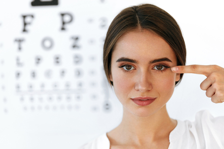 Health And Visual Concept. Closeup Of Beautiful Smiling Woman With Healthy Eyes In Front Of Visual Eye Test Board. Portrait Of Happy Girl Pointing At Her Eyes With Finger. High Resolution Image